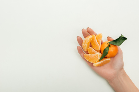 partial view of woman holding peeled tangerine slices and whole tangerine on white background Banco de Imagens