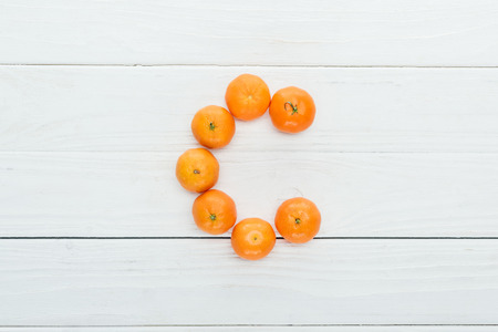 top view of letter c made of fresh tangerines on wooden white background