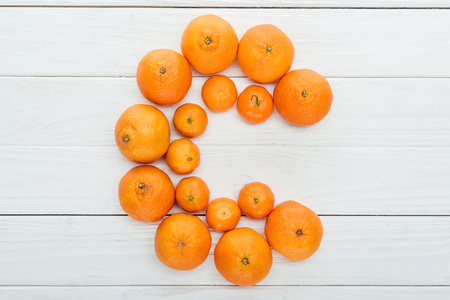 top view of letter C made of fresh tangerines on wooden white surface Stock Photo