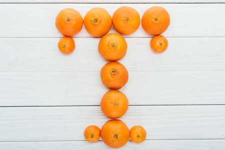 top view of letter T made of fresh tangerines on wooden white background