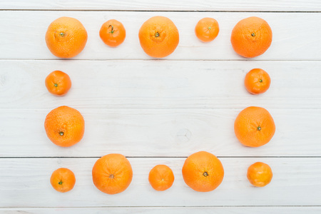 top view of square frame made of ripe orange tangerines on wooden white surface Stock Photo
