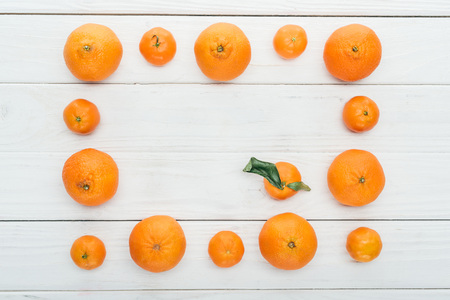 top view of square frame made of ripe orange tangerines on wooden white background