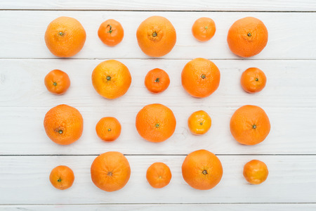 flat lay with big and small ripe tangerines on wooden white background Stock Photo