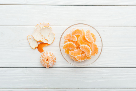 top view of peeled tangerine slices in glass bowl and peel on wooden white background