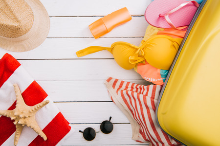 top view of sunscreen, starfish and summertime accessories and clothes in suitcase on white wooden background Archivio Fotografico