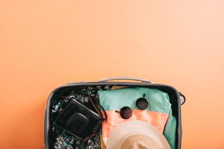 Vista superior de la maleta con accesorios de verano y cámara de película sobre fondo naranja