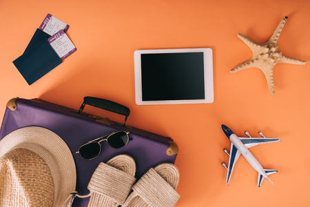 top view of summer accessories on travel bag, plane model, digital tablet and passports with tickets on orange background