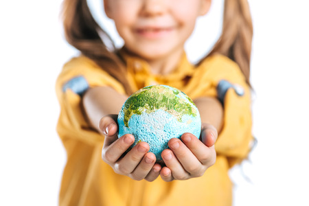 selective focus of cute child holding globe model in stretched hands isolated on white, earth day concept
