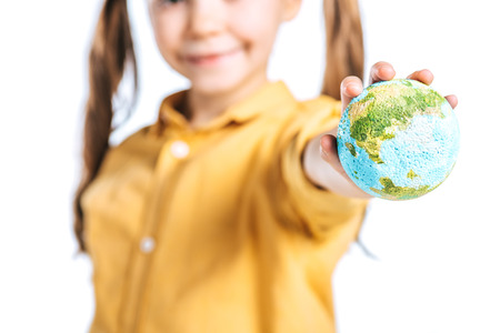 selective focus of smiling kid with globe model in stretched hand isolated on white, earth day concept
