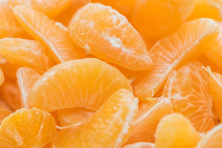 close up of bright orange tangerine peeled slices