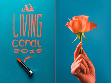 color of year 2019 handwritten lettering with coral lipstick, and partial view of coral colored female hand with coral rose on blue divided background Stok Fotoğraf