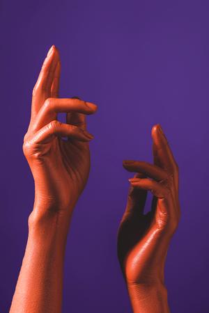 vue partielle de la femme gesticulant avec des mains de couleur corail sur fond violet, couleur du concept 2019 Banque d'images
