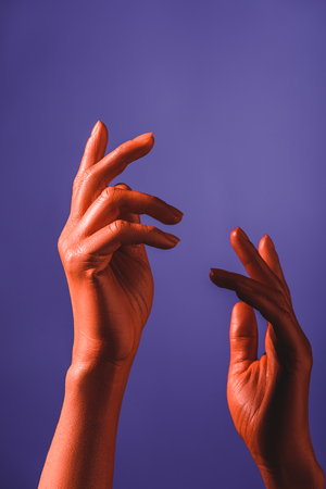 cropped view of coral colored female hands on violet background, color of 2019 concept Banque d'images