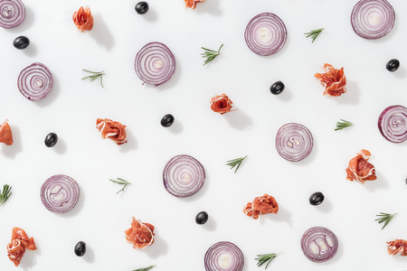 flat lay of red onion rings near prosciutto, cherry tomatoes, rosemary twigs and black olives on white background Stock Photo