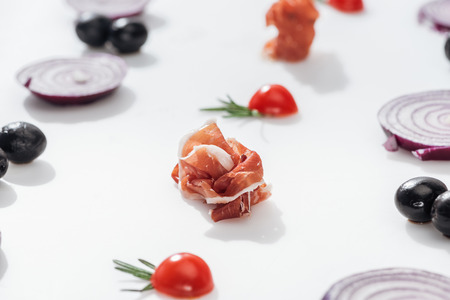 selective focus of tasty prosciutto near cherry tomatoes with rosemary twigs near red onion rings and black olives on white background