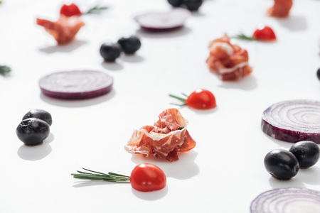 selective focus of prosciutto near cherry tomatoes with rosemary twigs near red onion rings and black olives on white background