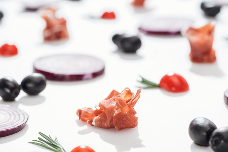 selective focus of delicious prosciutto near cherry tomatoes with rosemary twigs and red onion rings on white background Stock Photo