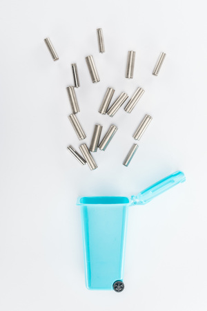 Top view of blue toy trashcan and batteries on grey background Stock Photo