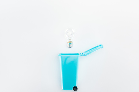 Top view of blue toy trashcan and bulb on grey background Stock Photo