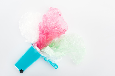 Top view of blue toy trashcan, pink and green plastic bags on grey background