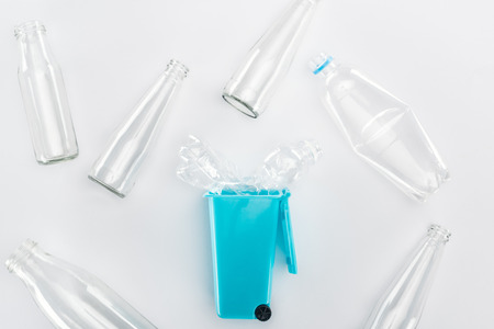 Top view of blue toy trashcan and empty plastic and glass bottles
