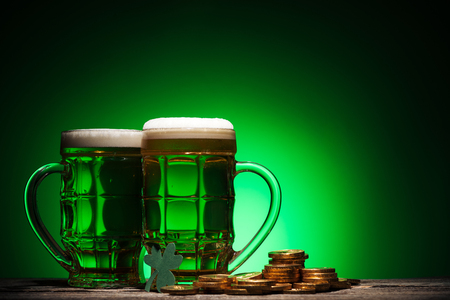 glasses of irish beer near golden coins on st patricks day on green background Stok Fotoğraf - 117898283