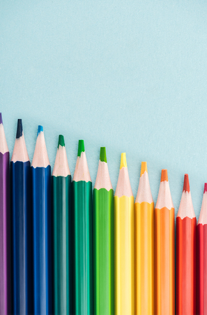 top view of rainbow multicolored pencils arranged in diagonal line on blue background, lgbt concept Stock Photo