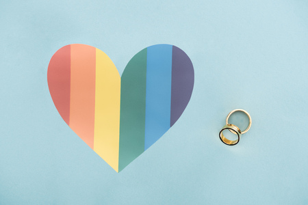 wedding rings on blue background with rainbow colored heart, lgbt concept Foto de archivo - 117909526