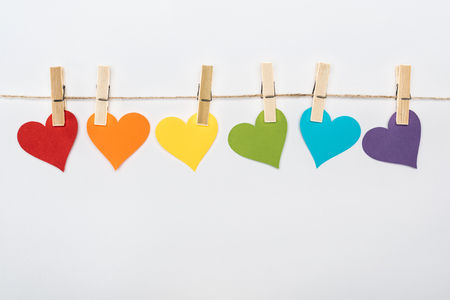 rainbow multicolored paper hearts on rope isolated on white, lgbt concept Foto de archivo