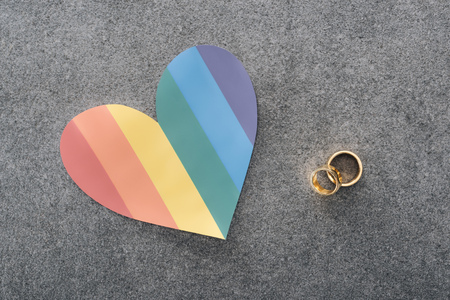 rainbow colored paper heart and wedding rings on grey background, lgbt concept Foto de archivo - 117898289