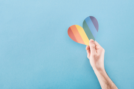 cropped view of male hand with rainbow colored paper heart on blue background, lgbt concept