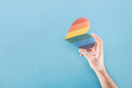 partial view of male hand with rainbow colored paper heart on blue background, lgbt concept Stock Photo