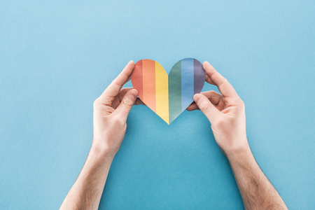 cropped view of male hands with rainbow colored paper heart on blue background, lgbt concept Stock Photo