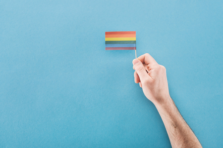 cropped view of man holding paper rainbow flag on blue background, lgbt concept Фото со стока