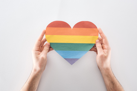partial view of man holding paper rainbow colored paper heart on grey background, lgbt concept