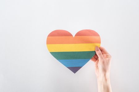 cropped view of female hand with rainbow colored paper heart isolated on grey, lgbt concept