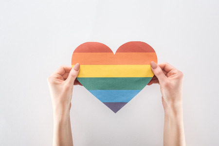 cropped view of female hands with rainbow colored paper heart isolated on grey, lgbt concept