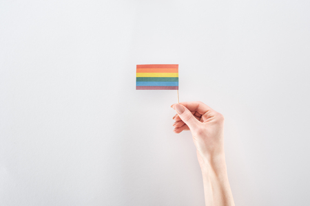 partial view of female hand with paper rainbow flag on grey background, lgbt concept