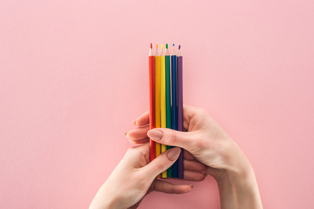 partial view of female hands with pencils of rainbow colors on pink background, lgbt concept Stock Photo