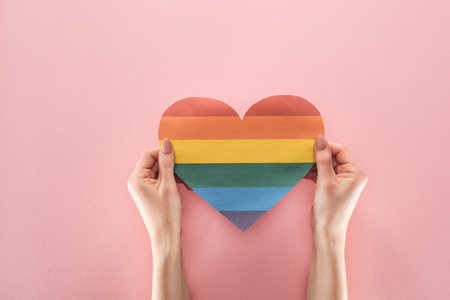 partial view of woman holding rainbow colored paper heart on pink background, lgbt concept