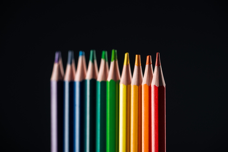 selective focus of rainbow colored pencils isolated on black, lgbt concept