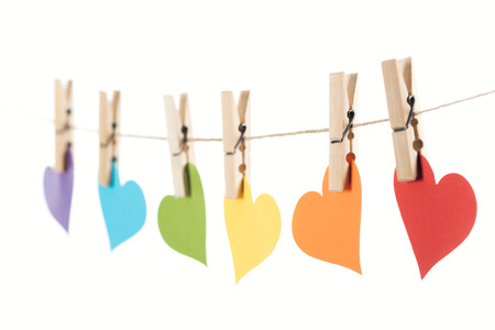 selective focus of rainbow multicolored paper hearts on rope isolated on white, lgbt concept