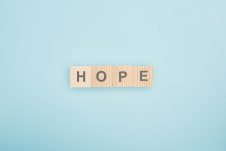 top view of hope lettering made of wooden cubes on blue background