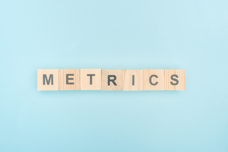 top view of metrics lettering made of wooden cubes on blue background 스톡 콘텐츠