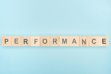 top view of performans lettering made of wooden cubes on blue background Stok Fotoğraf - 117898362