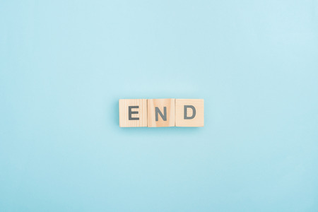 top view of end lettering made of wooden cubes on blue background