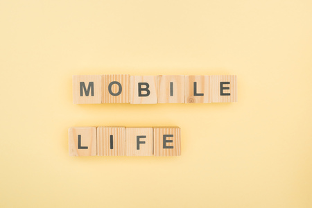 top view of mobil life lettering made of wooden cubes on yellow background