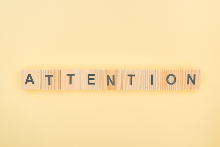 top view of attention lettering made of wooden cubes on yellow background
