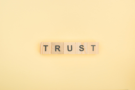 top view of trust lettering made of wooden cubes on yellow background Banco de Imagens