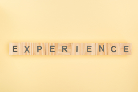 top view of experience lettering made of wooden cubes on yellow background Stock fotó